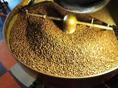 Coffee beans being stirred around in a roasting machine.