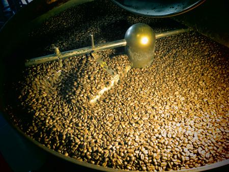 Coffee beans being stirred around in a roasting machine. photo