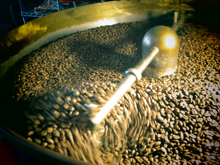 stirred: Coffee beans being stirred around in a roasting machine.