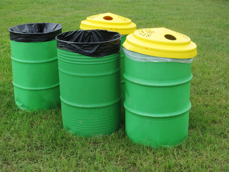 Green trash barrels organized for waste and recycling.  Stock Photo
