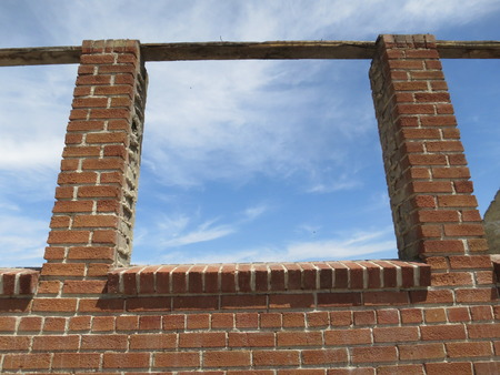A window frame on an old brick building structure with a blue sky background. photo