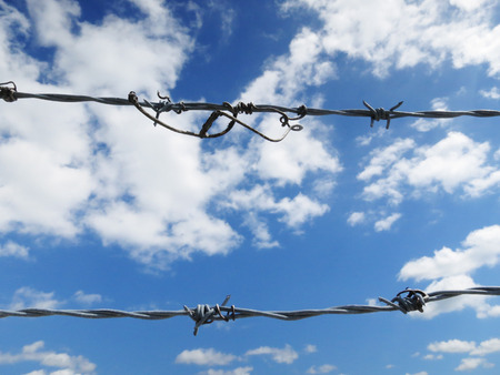 Barbed wire against a cloudy blue sky. photo