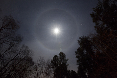A Lunar halo phenomenon around full moon which is formed by moonlight passing through ice crystals in the atmosphere.