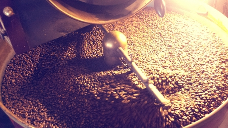 roasting: Coffee beans being stirred around in a roasting machine.
