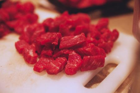 cubed: A pile cut raw beef chunks on a cutting board.