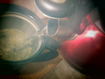 loose leaf: A view of steaming hot water being poured from tea kettle into a french press filled with loose leaf Yerba Mate.