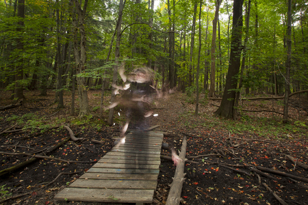 ghostly: A ghostly figure on a forest bridge. Stock Photo