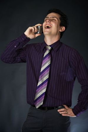 successfull: Laughing young man using a cellphone