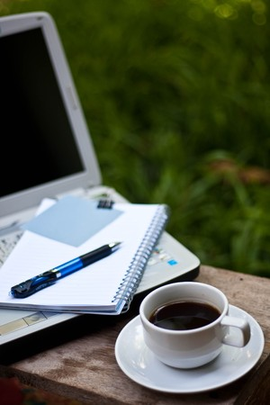 home office desk: paper note on notbook with coffee in garden.