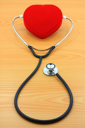 red heart ane stethoscope on wood background photo