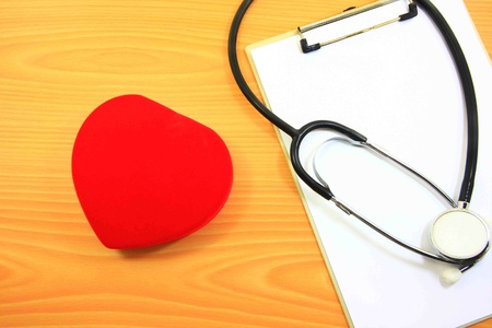 red heart and stethoscope on wood background photo