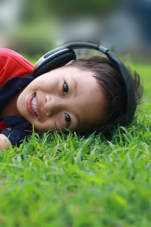 freetime: little boy and headphone on green glass