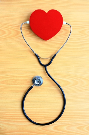 red heart and stetoscope on wood background Stock Photo