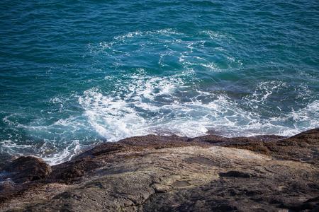 Characteristics of the wave Crashing into rocks photo