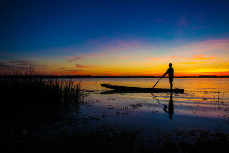 Silhouette of a man fishing boat  photo