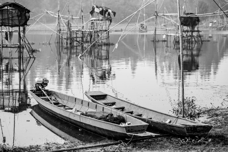Black and white image of a wooden boat of fishermen  photo