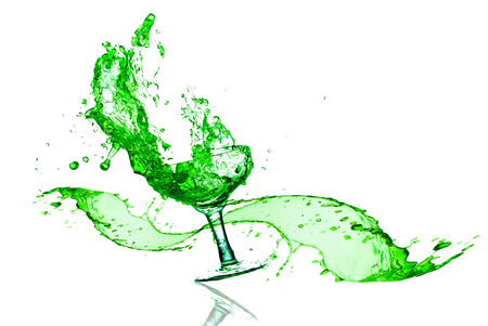 green splashes out drink from glass on a white background  photo