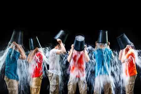 seau d eau: homme verser un seau de glace, mettez-vous sur un fond noir Banque d'images
