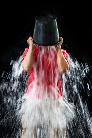 challenging: man pour a bucket of ice, put yourself on a black background