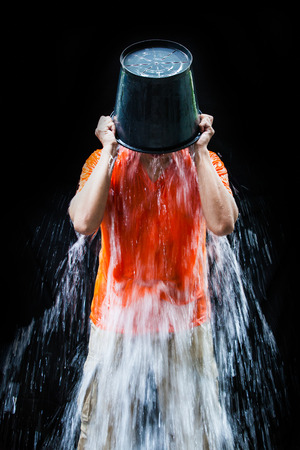 gehrig: man pour a bucket of ice topped their head on a black Stock Photo