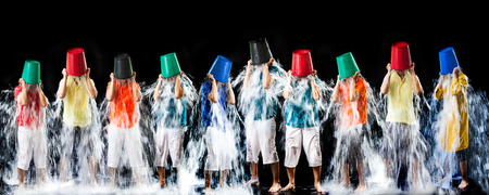 panormic of the man pour a bucket of ice topped their head on a black Foto de archivo