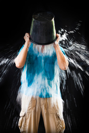 man pour a bucket of ice topped their head on a black Stock Photo