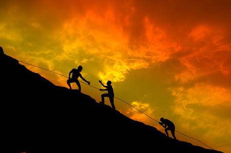 trails: Silhouettes of people are climbing. Stock Photo