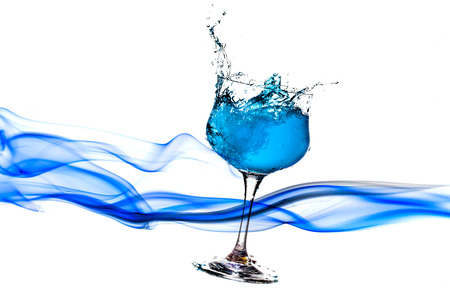 cocktail glasses: blue water splash from glass on white background.