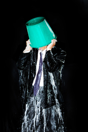 himself: Man pour out bucket of water pouring himself. Stock Photo