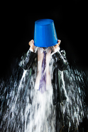 challenge: Man pour out buckets of water pouring himself. Stock Photo