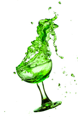 absinthe: Drink green splash out of glass on a white background.