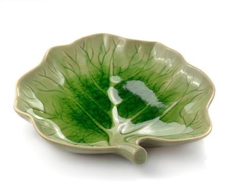 dinky: Green ceramic plate on a white background . Stock Photo