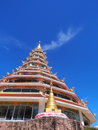 thaiart: Chinese-styled pagoda in Thailand temple under blue sky