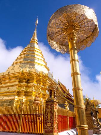 Golden pagoda of Wat Phra That Doi Suthep under cloudy blue sky in Chiangmai, Thailand photo