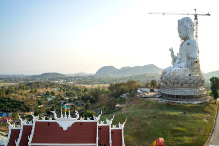 goddess of mercy: The Goddess of Compassion and Mercy (Guan Yim goddess) constructed giant statue in Thai temple under twilight sky Stock Photo