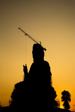 goddess of mercy: Silhouette of The Goddess of Compassion and Mercy (Guan Yim goddess) constructed giant statue in Thai temple under twilight sky