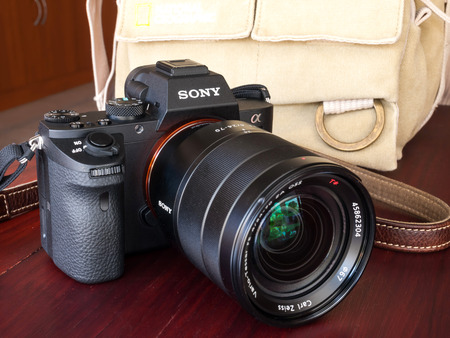carl: BANGKOK - FEBRUARY 19: Sony digital camera model A7II with normal Carl Zeiss zoom lens 24-70 mm f4 in natural light on red wooden table, was taken on February 19, 2015, in Bangkok Thailand.