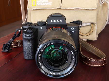 national geographic: BANGKOK - FEBRUARY 19: Sony digital camera model A7II with normal Carl Zeiss zoom lens 24-70 mm f4 in natural light on red wooden table, focus on brand logo, was taken on February 19, 2015, in Bangkok Thailand.