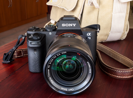 national geographic: BANGKOK - FEBRUARY 19: Sony digital camera model A7II with normal Carl Zeiss zoom lens 24-70 mm f4 in natural light on red wooden table, was taken on February 19, 2015, in Bangkok Thailand.