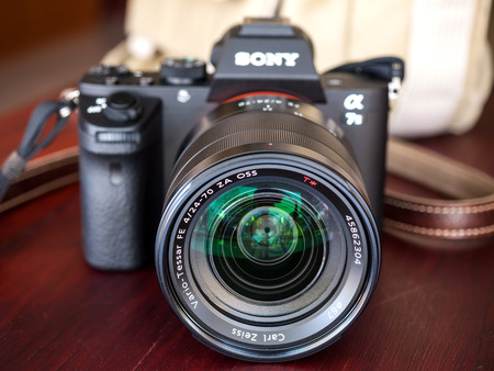 carl: BANGKOK - FEBRUARY 19: Sony digital camera model A7II with normal Carl Zeiss zoom lens 24-70 mm f4 in natural light on red wooden table, focus on front surface of the lens, was taken on February 19, 2015, in Bangkok Thailand. Editorial