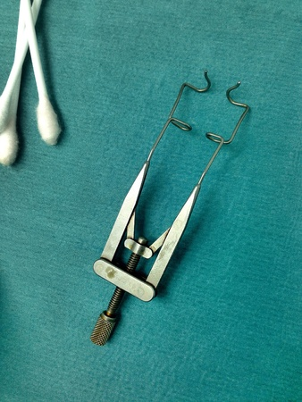 Eye speculum on green sterile paper in operating room