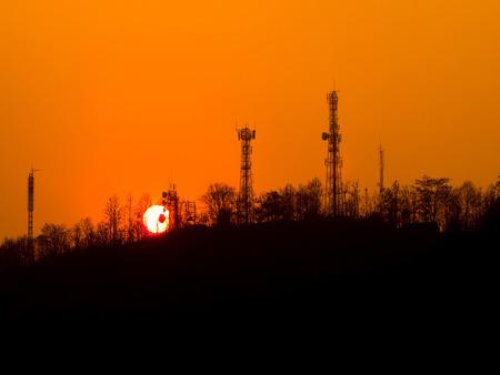 Sunset over urban mountain on orange evening sky photo