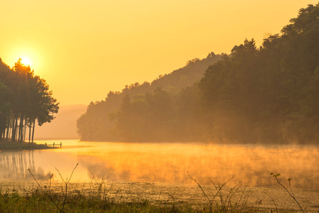 Pang Oung is pretty and serene lake in a valley glittering with sunlight in morning sunrise surrounded by mountains photo