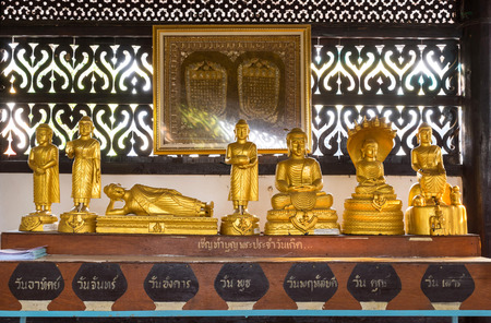 describe: Golden buddha statues in various actions for each day of birth, in Thai temple. The Thai letters describe for day in week from Monday to Saturday.