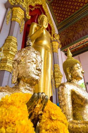 attached: Gold attached buddha statue stand with main standing golden buddha statue in The First Grand Pagoda in Nakornpathom, Thailand Stock Photo