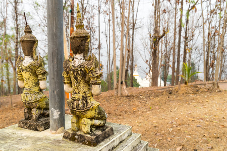 respected: Respected angel statue with white pagoda background in Wat Phra That Doi Gongmu in Maehongson, Thailand Stock Photo