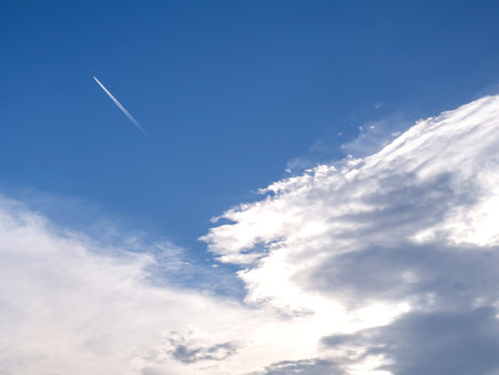 contrail: Cloudy blue sky with aircraft contrail Stock Photo