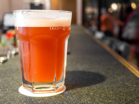 large size: Draft beer in large size glass on counter bar in pub