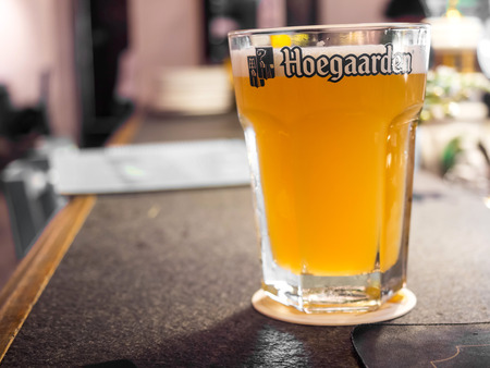 large size: BANGKOK - MAY 16: Hoegaarden draft beer in large size glass on counter bar in pub was taken in Bangkok, Thailand, on May 16, 2015.