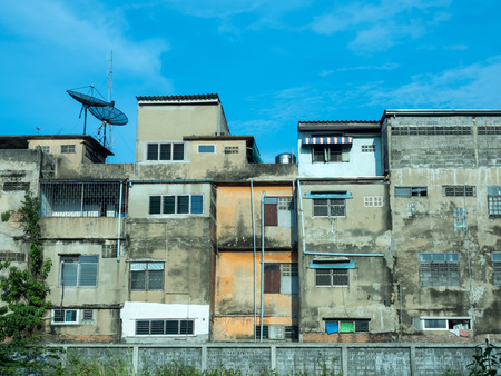 needy: Old pile and ruined resident buildings in Bangkok under blue sky Stock Photo
